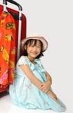 坐在一次巨大的旅行红色su附近的织法帽子的小亚裔女孩 免版税库存照片