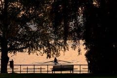 坐在一艘皮船的人剪影在晚上 免版税图库摄影
