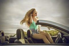 坐在一辆优等的汽车的端庄的妇女 免版税库存图片