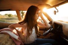 坐在一辆减速火箭的汽车的太阳镜的年轻俏丽的妇女 库存图片