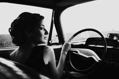 坐在一辆减速火箭的汽车的美丽的夫人 库存图片