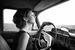 坐在一辆减速火箭的汽车的美丽的夫人 免版税库存照片