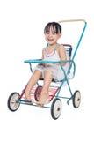 坐在一辆减速火箭的婴儿推车的亚裔中国小女孩 免版税库存图片
