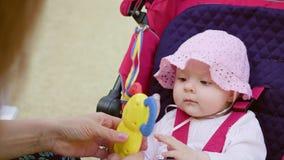 坐在一辆婴儿推车的婴孩` s在公园 库存图片