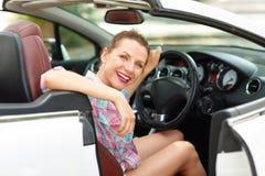 坐在一辆敞篷车汽车的年轻俏丽的妇女 免版税图库摄影