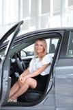 坐在一辆新的汽车的客舱的成功的少妇 库存照片