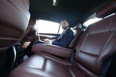 坐在一辆有名望的汽车的后座的微笑的商人 免版税图库摄影