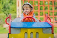 坐在一辆木汽车的男孩在操场 图库摄影