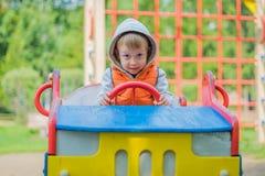 坐在一辆木汽车的男孩在操场 免版税库存照片