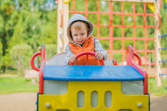 坐在一辆木汽车的男孩在操场 免版税库存图片