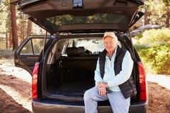 坐在一辆汽车的开放后车箱的老人在森林里 库存图片