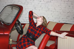 坐在一辆红色汽车的美丽的女孩 库存图片