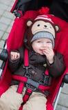坐在一辆红色婴儿推车的愉快的男婴 库存照片