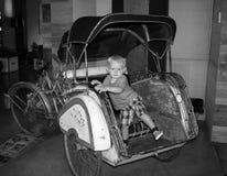 坐在一辆老时尚汽车的一个年轻小孩 免版税库存照片