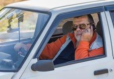 坐在一辆老汽车的一个老人的画象 免版税库存照片