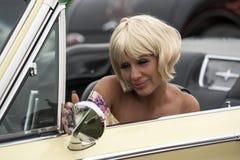 坐在一辆老汽车的白肤金发的画报 库存照片