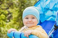 坐在一辆蓝色婴儿推车和笑的半年老逗人喜爱的快乐的男孩步行的在夏天 库存图片
