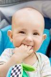坐在一辆蓝色婴儿推车的愉快的男婴 免版税库存图片