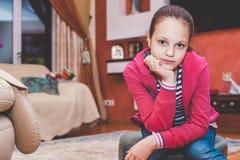 坐在一间舒适屋子的女孩 免版税库存照片