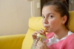 坐在一黄色沙发饮用的橙汁过去的年轻十几岁的女孩 库存图片