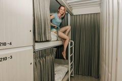坐在一间时髦的旅舍卧室的女孩 库存照片