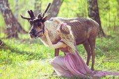 坐在一件美妙的礼服的女孩的画象在驯鹿旁边 免版税库存图片