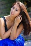 坐在一件蓝色礼服的美好的亚洲模型 图库摄影