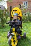 坐在三轮车的孩子 免版税库存图片