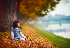坐在下落的叶子的愉快的女孩在秋天公园 库存图片