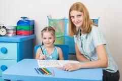 坐在与一个五年女孩的一张与拼写的桌和成交上的女孩 库存照片