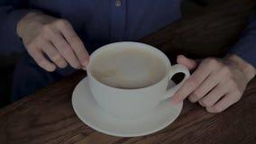 坐在与一个杯子的一个咖啡馆的美女热奶咖啡 股票录像
