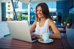 坐在与一个杯子的室外café的年轻女实业家coffe 库存照片