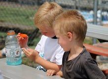 坐在与一个瓶的一张桌上的两个年轻男孩Gatorade 库存照片