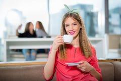 坐在与一个白色杯子的咖啡馆的年轻美丽的少年女孩, 库存图片
