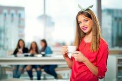 坐在与一个白色杯子的咖啡馆的年轻美丽的少年女孩, 免版税图库摄影