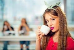 坐在与一个白色杯子的咖啡馆的年轻美丽的少年女孩, 免版税库存图片