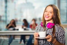 坐在与一个白色杯子的咖啡馆的年轻美丽的少年女孩, 免版税库存照片