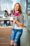 坐在与一个白色杯子的咖啡馆的年轻美丽的少年女孩, 库存照片