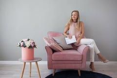 坐在与一个笔记本的一把椅子的年轻友好的妇女在她的手上 时髦的室内设计,花花束  库存图片