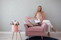 坐在与一个笔记本的一把椅子的年轻友好的妇女在她的手上 时髦的室内设计,花花束  免版税图库摄影