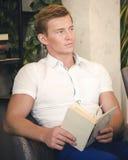 坐在与一本书的一把椅子的可爱的年轻人在他的手上 免版税库存照片