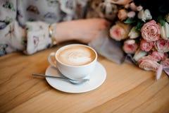 坐在与一杯咖啡的木桌上的女孩和美丽的花束 免版税库存图片
