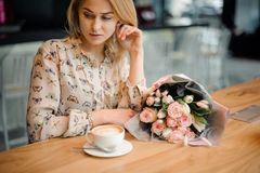 坐在与一杯咖啡的桌上的女孩和美丽的花束 库存图片