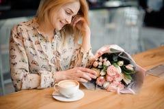 坐在与一杯咖啡的桌上的微笑的女孩和美丽的花束 免版税库存图片