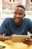 坐在与一种数字式片剂的一个咖啡馆的年轻黑人 图库摄影
