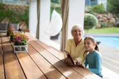 坐在与一种数字式片剂的一片甲板树荫下的孙女和祖母 库存图片