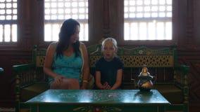 坐在与东部内部,与手肚皮舞的妇女跳舞的咖啡馆的母亲和女儿 股票视频