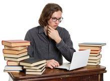 坐在与书和膝上型计算机的一张桌上的年轻人 免版税库存图片
