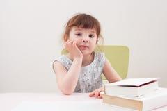 坐在与书的一张桌上的一件蓝色礼服的女孩 免版税库存图片