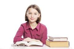 坐在与书的一张桌上的微笑的青少年的女孩 r 免版税库存图片